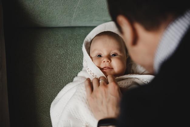Homem brinca com um pequeno bebê recém-nascido envolto em cobertor macio
