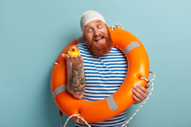 Homem brincalhão e alegre com barba ruiva espessa, segura um patinho de brinquedo e se diverte na praia