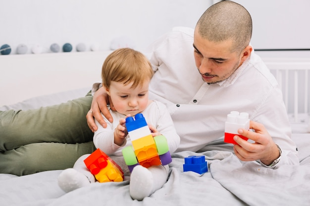 Homem brincando com bebezinho segurando blocos de construção de brinquedo