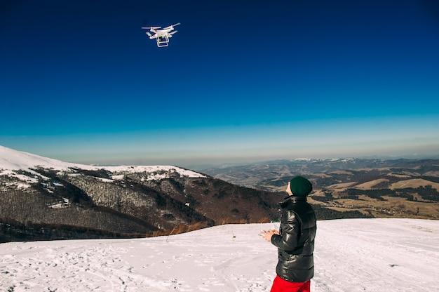 Homem brincando com o drone. silhueta contra o céu do por do sol