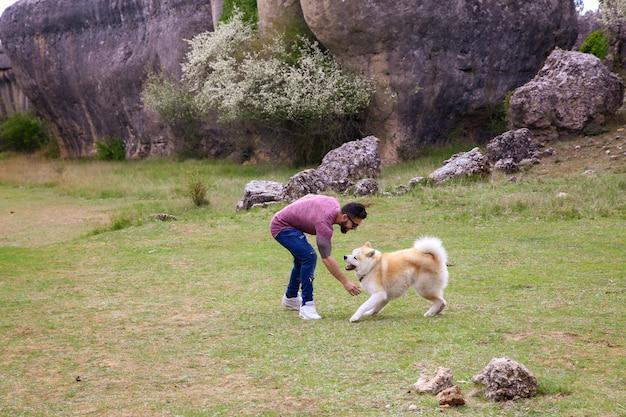 Homem brincando com seu cachorro no campo