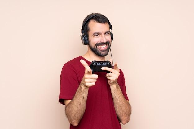 Homem brincando com um controlador de videogame sobre parede isolada, apontando para a frente e sorrindo