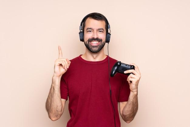 Homem brincando com um controlador de videogame sobre parede isolada apontando uma ótima idéia