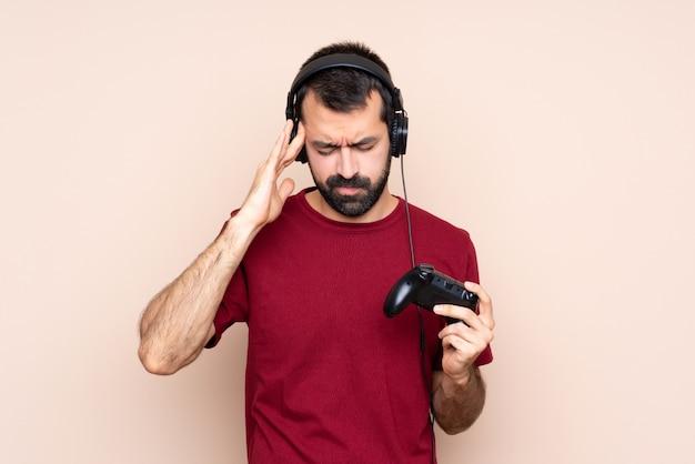 Homem brincando com um controlador de videogame sobre parede isolada com dor de cabeça