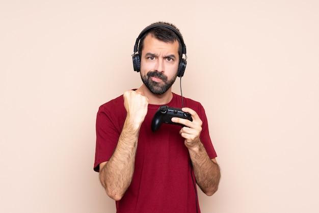 Homem brincando com um controlador de videogame sobre parede isolada com gesto de raiva