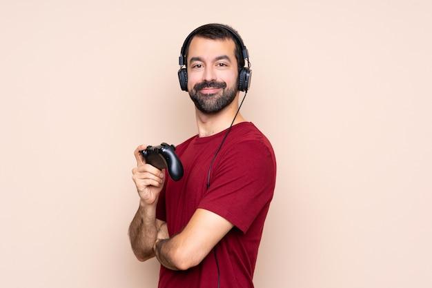 Homem brincando com um controlador de videogame sobre parede isolada com os braços cruzados e olhando para a frente