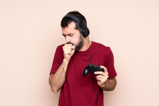 Homem brincando com um controlador de videogame sobre parede isolada está sofrendo de tosse e se sentindo mal