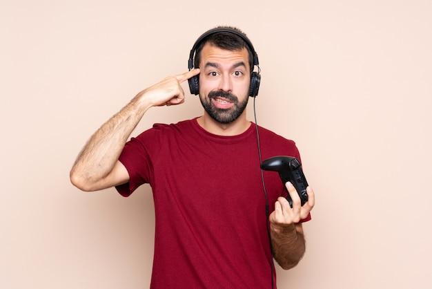 Homem brincando com um controlador de videogame sobre parede isolada, fazendo o gesto de loucura, colocando o dedo na cabeça