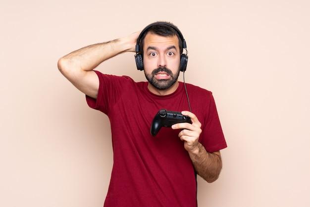 Homem brincando com um controlador de videogame sobre parede isolada frustrado e leva as mãos na cabeça