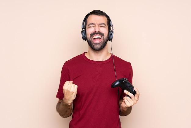 Homem brincando com um controlador de videogame sobre parede isolada, gritando para a frente com a boca aberta