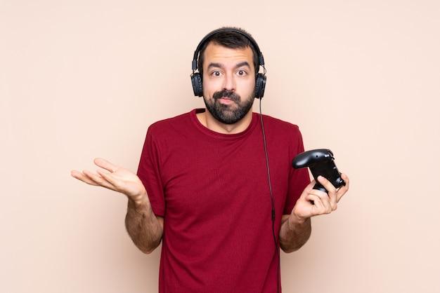 Homem brincando com um controlador de videogame sobre parede isolada infeliz por não entender algo