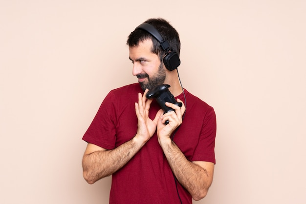 Homem brincando com um controlador de videogame sobre parede isolada planejando algo