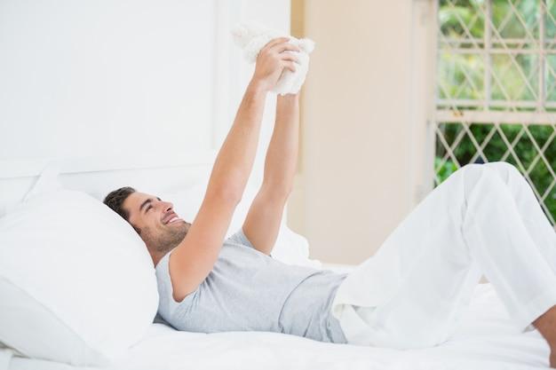 Homem brincando com ursinho de pelúcia na cama