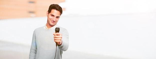Homem bronzeado bonito jovem com um microfone