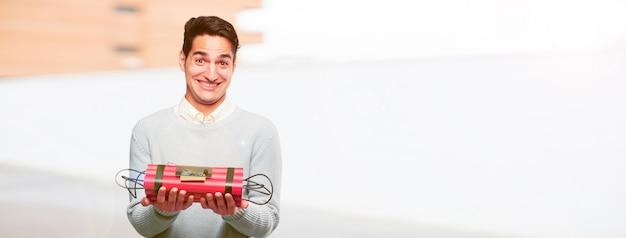 Homem bronzeado bonito jovem com uma bomba de dinamite