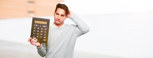 Homem bronzeado bonito jovem com uma calculadora