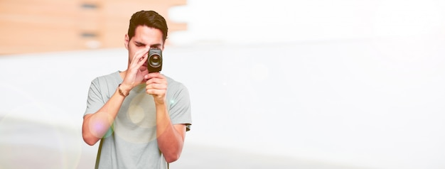 Homem bronzeado bonito jovem com uma câmera de cinema vintage