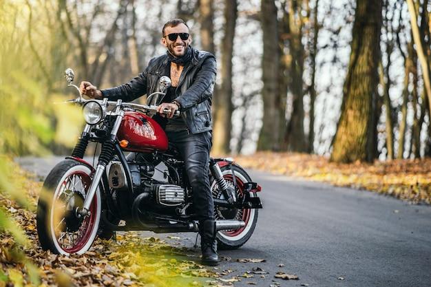 Homem brutal barbudo de óculos escuros e jaqueta de couro, sentado em uma motocicleta na estrada na floresta