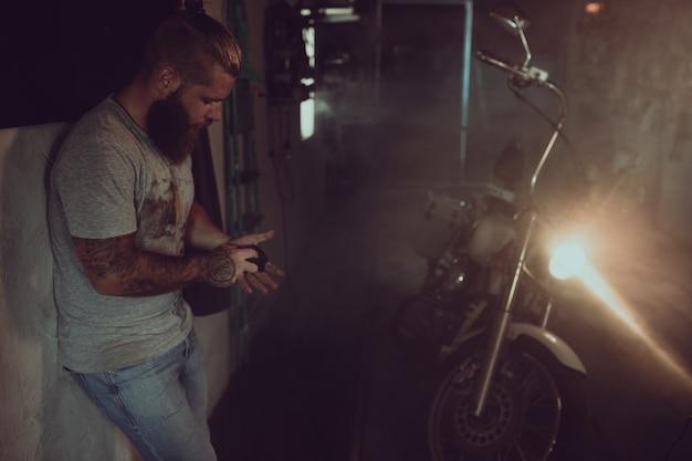 Homem brutal bonito com uma barba está de pé em sua garagem no contexto de uma motocicleta e olhando para longe