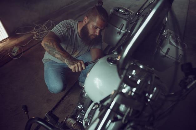 Homem brutal bonito com uma barba que repara uma motocicleta em sua garagem
