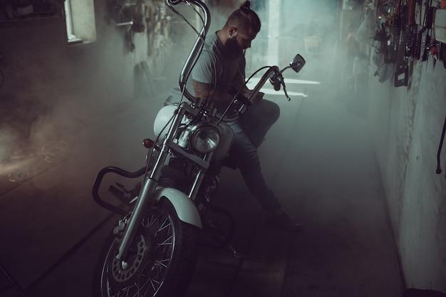 Homem brutal bonito com uma barba, sentado em uma motocicleta em sua garagem, limpando as mãos e olhando para o lado