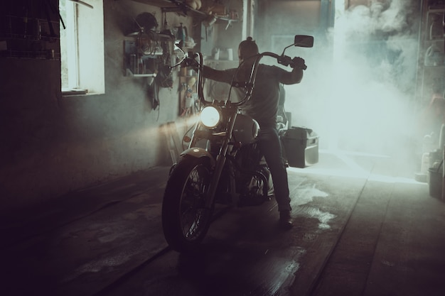 Homem brutal bonito com uma barba, sentado em uma motocicleta em sua garagem