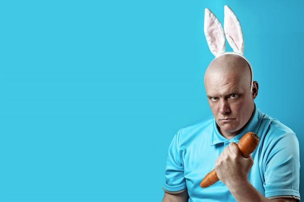 Homem brutal careca em t-shirt leve e orelhas de coelho. em suas mãos, ele segura a cenoura como um haltere.