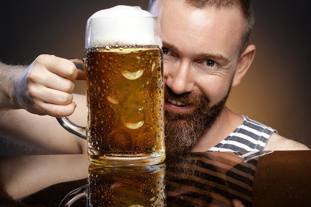 Homem brutal com um copo de cerveja