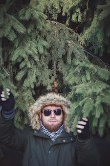 Homem brutal com uma jaqueta de inverno e óculos escuros em um fundo de abeto verde
