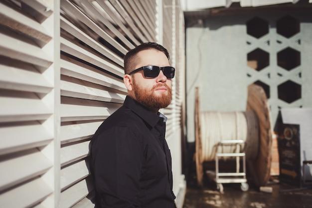 Homem brutal em óculos de sol com uma barba