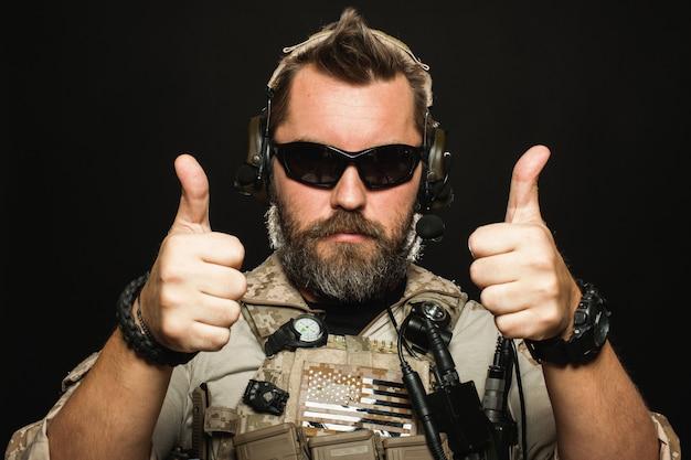 Homem brutal em uniforme militar mostra dois dedos para cima.