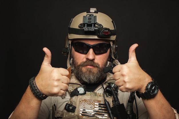 Homem brutal em uniforme militar mostra dois dedos.