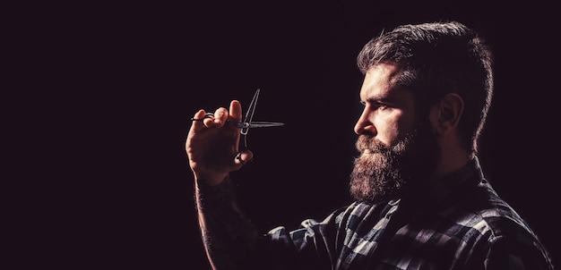 Homem brutal, moderno com bigode. homem na barbearia, corte de cabelo, barbear. corte de cabelo do homem na barbearia. perfil de homem de barba elegante, tesoura. tesouras de barbeiro, barbearia. copie o espaço.