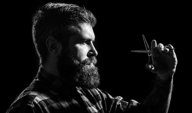 Homem brutal, moderno com bigode. homem na barbearia, corte de cabelo, barbear. corte de cabelo do homem na barbearia. perfil de homem de barba elegante, tesoura. tesouras de barbeiro, barbearia. preto e branco.