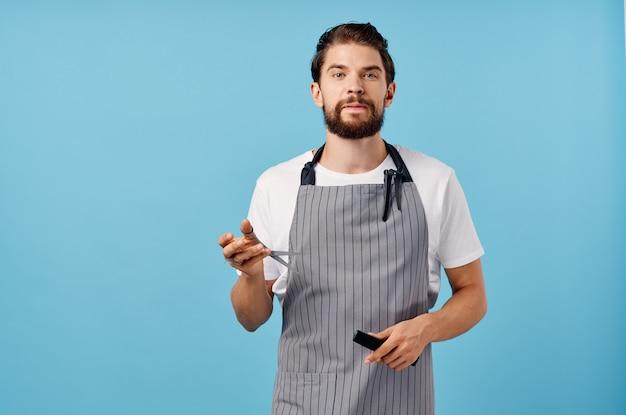 Homem cabeleireiro em tesoura de avental cinza pente morena barba grossa barbearia. foto de alta qualidade