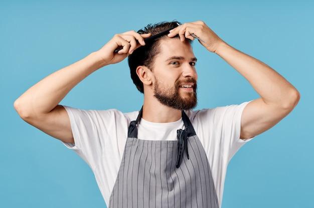 Homem cabeleireiro profissional com um avental cinza arruma o cabelo em uma parede azul e um pente de tesoura.