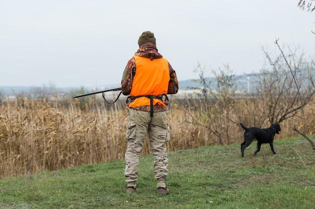 Homem caçador camuflado com uma arma durante a caça em busca de aves selvagens ou de caça. temporada de caça de outono.