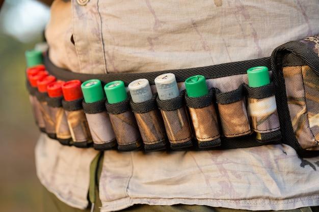 Homem caçador camuflado com uma arma durante a caça em busca de aves selvagens ou de caça. temporada de caça de outono. Foto Premium