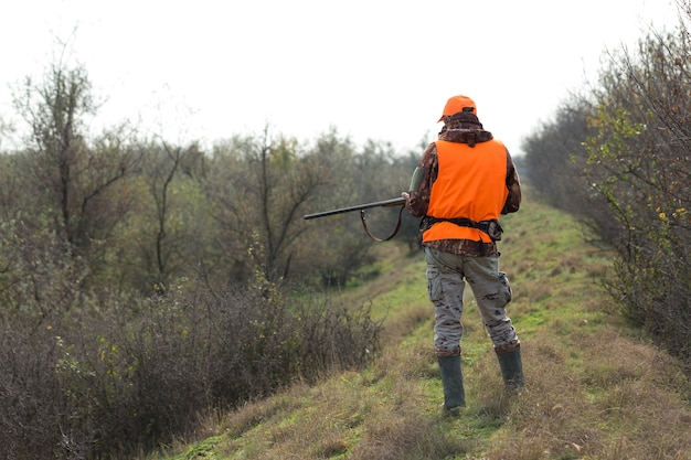 Homem caçador camuflado com uma arma durante a caça em busca de pássaros selvagens ou de caça