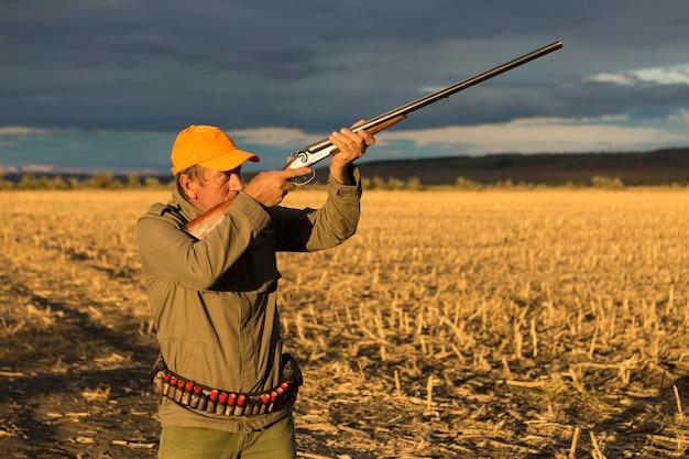 Homem caçador camuflado com uma arma durante a caça em busca de pássaros selvagens