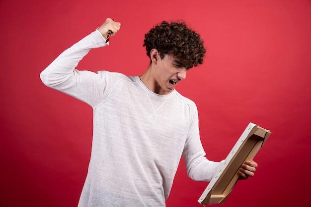 Homem cacheado com raiva, gritando para uma tela vazia.