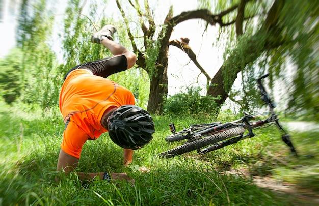 Homem caindo da bicicleta no caminho no campo