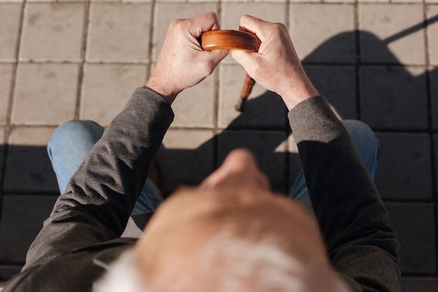 Homem calmo, cansado, arrumado, sentado no banco, descansando e tomando sol