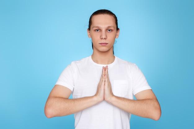 Homem calmo de mãos dadas em gesto de ioga, relaxando, meditando, tentando se acalmar sobre fundo azul