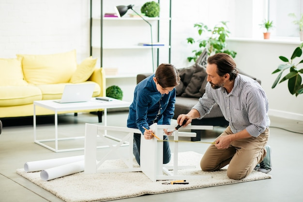 Homem calmo de meia-idade sentado no chão com uma chave de fenda em uma das mãos e medindo o comprimento da perna da cadeira com seu entusiasmado filho adolescente
