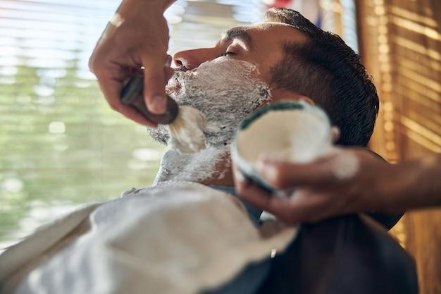 Homem calmo de olhos fechados coberto de creme de barbear durante consulta em uma barbearia