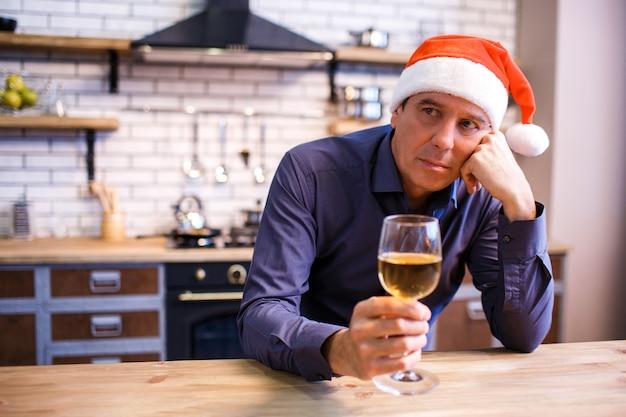 Homem calmo e pensativo calmo na cozinha, segurando o copo de vinho