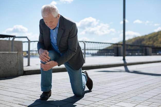 Homem calmo e triste, de pé sobre um joelho, segurando as mãos de outro, enquanto sofre de dor