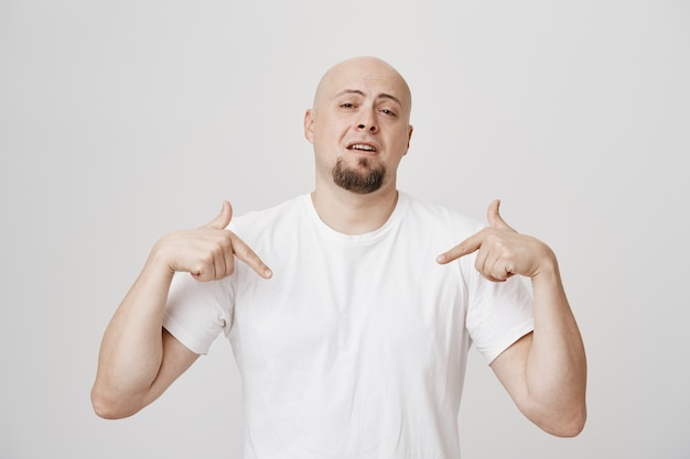 Homem calvo de meia-idade confiante apontando a si mesmo para se exibir, se gabando