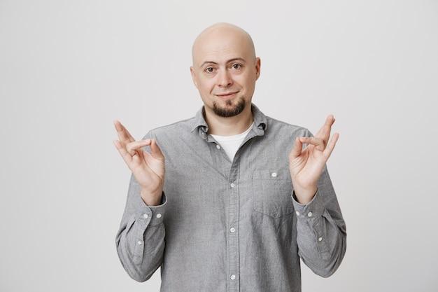 Homem calvo e despreocupado de meia-idade mostrando sinais de rock-n-roll